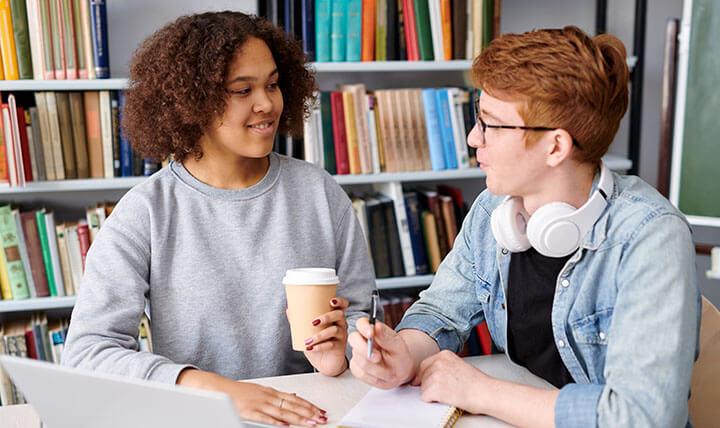 Dois adolescentes conversando em uma biblioteca